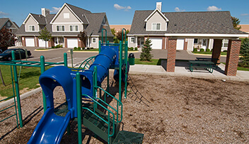 Exterior photo of tot lot and picnic pavillion at a workforce housing development.