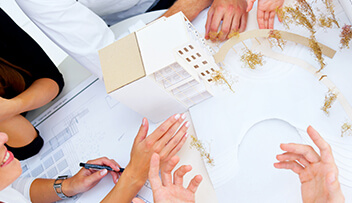 Stock photo - architectural model of building with hands of people discussing the model