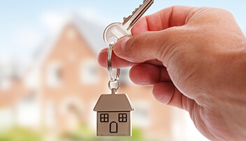 Stock photo - hand holding a key on a house keyring.
