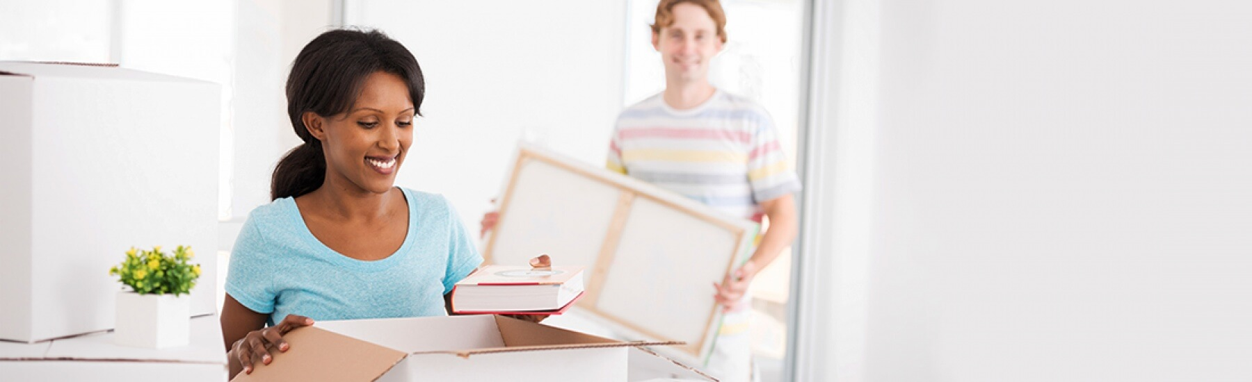 Stock Photo - woman and man unpacking boxes.