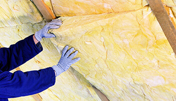 Stock photo - insulation being placed in ceiling.