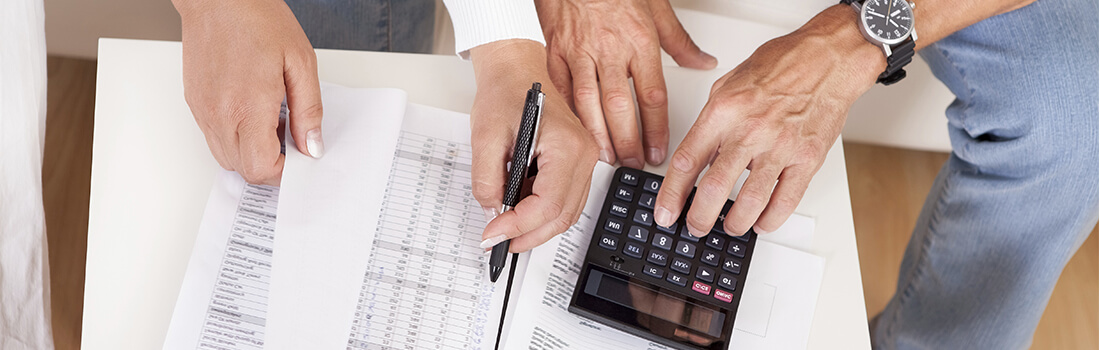 Stock photo - woman and man reviewing paperwork with calculator.