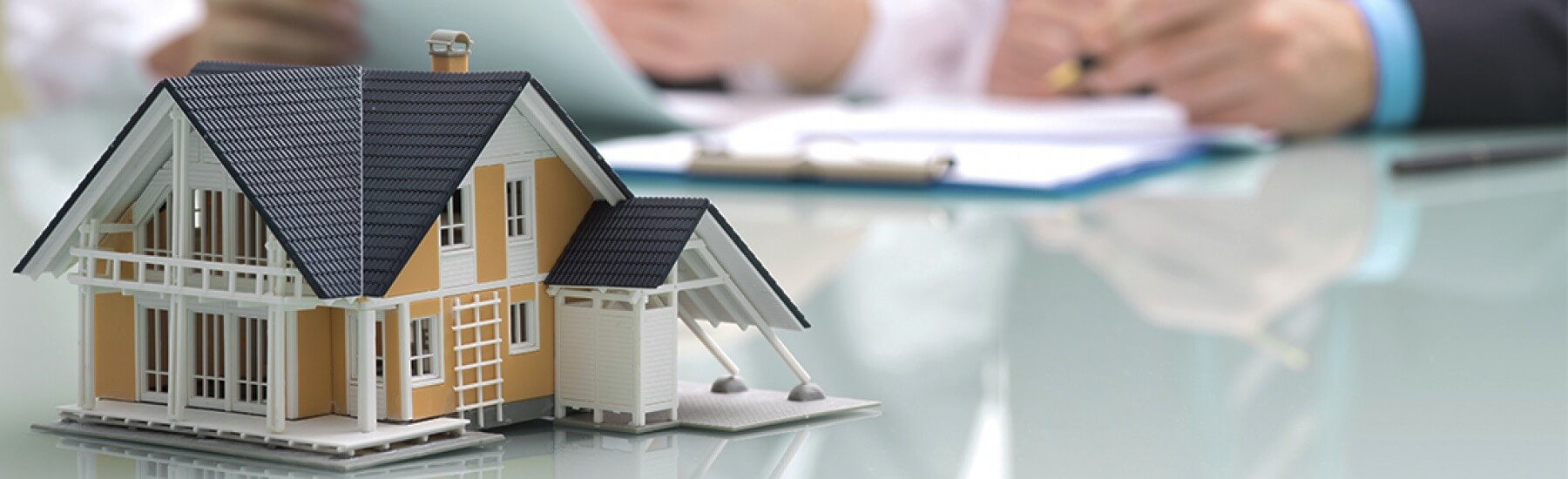 Stock photo - small model of house on table with people reviewing paperwork in the background.